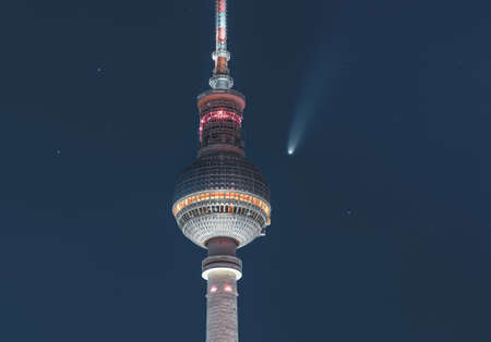 Neowise Comet visible in city of Berlin over TV tower with illuminated night sky. Astro photo during night time with stars. Capital of Germany.