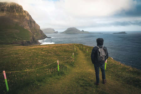 Young man tourist standing on Faroe islands with stormy view towards mykines on the island of Vagar as seen from mulafossur waterfall. Low clouds with atlantic ocean waves.
