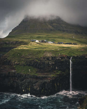 Aerial drone panorama of Gasadalur village and Mulafossur its iconic waterfall, Vagar, Faroe Islands, Denmark. Rough see in the north atlantic ocean. Lush greens during summer. Banco de Imagens