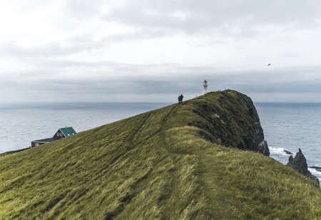 View Towards Lighthouse on the island of Mykines Holmur, Faroe Islandson a cloudy day with view towards Atlantic Ocean.