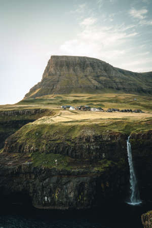 Gasadalur village and Mulafossur its iconic waterfall during sunset in summer with bluw sky. Vagar, Faroe Islands, Denmark. Rough see in the north atlantic ocean.