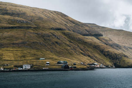 View towards small lighthouse on faroe islands on a sunny day with clouds over the atlantic ocean. Banco de Imagens