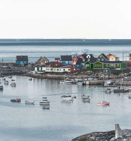 The colorful house of Ilulissat, Greenland. Kangia icefjord covered in fog in background with icebergs. Global Warming concept.
