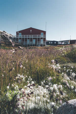 Typical wooden colourful fisher house with iceberg in Disko bay area Greenland and Ilulissat. Typical architecture in the arctic circle. Summer and blue sky.