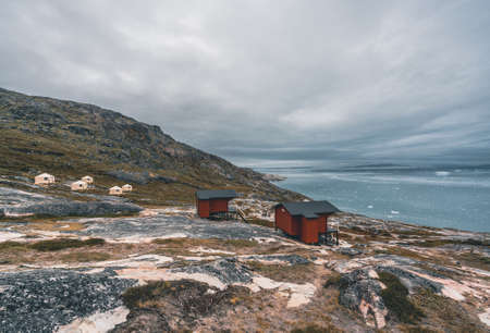 Panoramic image of Camp Eqi at Eqip Sermia Glacier in Greenland. nature landscape with lodge cabins. Midnight sun and pink sky. Tourist destination Eqi glacier in West Greenland AKA Ilulissat and Jakobshavn Glacier. Heavlly affected by Global Warming. Photo taken in Greenland