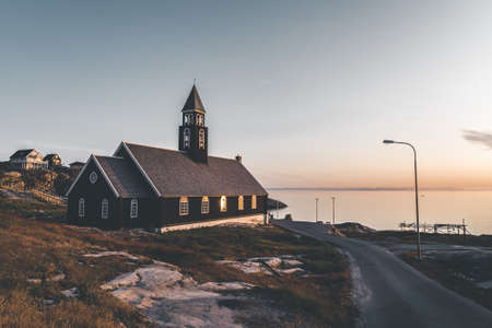 Old wooden Zions Church in arctic city of Ilulissat, with midnight sun light and blue sky in North Greenland