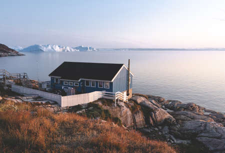 The colorful house of Ilulissat, Greenland. Kangia icefjord covered in fog in background with icebergs. Global Warming concept. Banco de Imagens