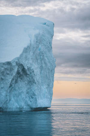 Arctic nature landscape with icebergs in Greenland icefjord with midnight sun sunset sunrise in the horizon. Early morning summer alpenglow during midnight season. Ilulissat, West Greenland. Banco de Imagens