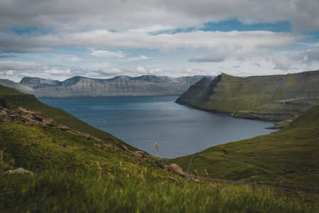 Spectacular views of the scenic fjords on the Faroe Islands near the village Funningur with mountains during a sunny spring day.