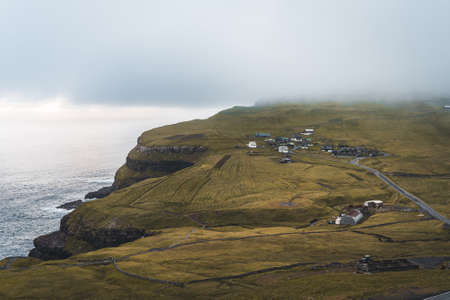 Bour village Grass-covered picturesque houses at the Faroese coastline in the village Bour with view onto Dranganir and Tindholmur during spring.