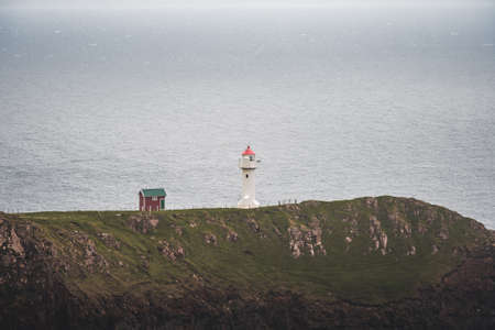 View towards orange house on Akraberg lighthouse at Suduroy island at summer, Faroe Islands. Banco de Imagens