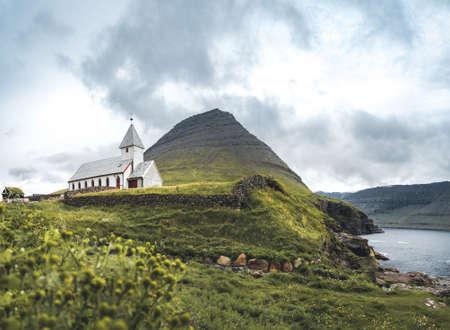 View onto the church of Vidareidi also named Vidareidi Kirkja with moody cloudy sky, fog and mountains. Faroe Islands, Denmark, Europe.