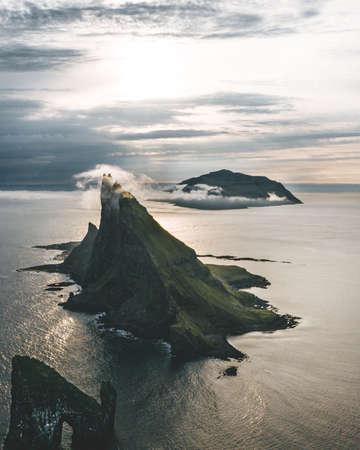 Drangarnir and Tindholmur on Faroe Islands Vagar, aerial drone view during sunset in North Atlantic Ocean. Faroe Islands, Denmark, Europe.