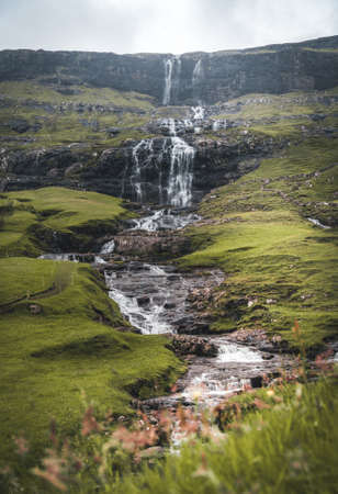 Waterfalls in the village of Saksun on the Faroe islands. No people around, traditional stone houses.