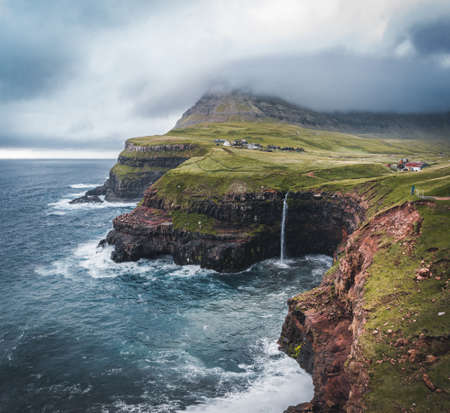 Aerial drone view of Gasadalur village and Mulafossur its iconic waterfall, Vagar, Faroe Islands, Denmark. Rough see in the north atlantic ocean. Lush greens during summer. Banco de Imagens