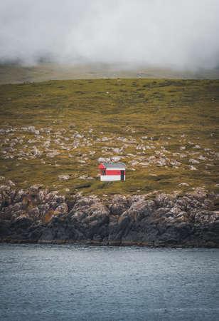 Black house on famous faroese Witches Finger Trail and Koltur island on background. Sandavagur village, Vagar island, Faroe islands, Denmark. Landscape photography Banco de Imagens