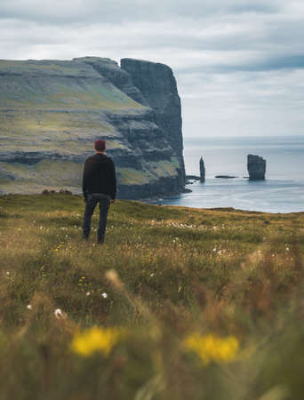 Young man tourist standing in front of Risin and Kellingin rocks in the sea as seen from Tijornuvik bay on Streymoy on the Faroe Islands, Denmark, Europe