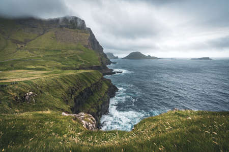 Faroe islands with stormy view towards Tindholmur and Drangarnir on the island of Vagar as seen from mulafossur waterfall. Low clouds with atlantic ocean waves. Banco de Imagens