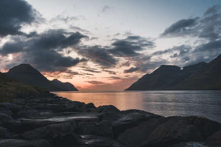 Faroe Islands Kalsoy in sunset light durig twilight with pink sky and cliffs.