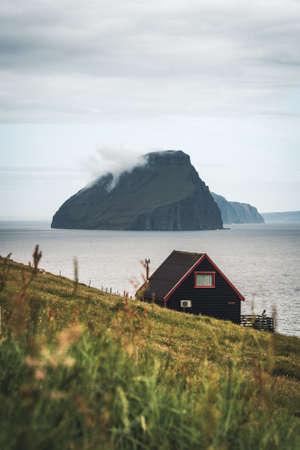 Black house on famous faroese Witches Finger Trail and Koltur island on background. Sandavagur village, Vagar island, Faroe islands, Denmark. Landscape photography. Photo taken in Faroe Islands, Denmark, Europe. Banco de Imagens