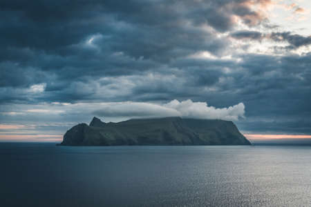 Faroe islands View Towards island of Mykines Holmur, during sunset and twilight on a cloudy day with view towards Atlantic Ocean. Banco de Imagens