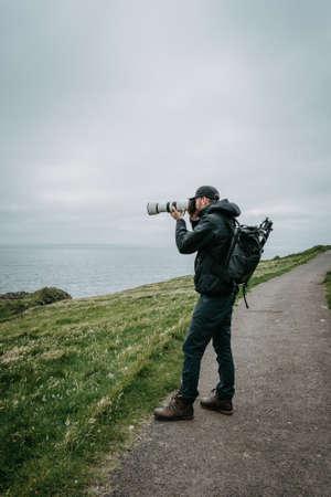 Young man trourist traveler hiking. Tjornuvik beautiful town in the Faroe Islands, sit on the north coast of Streymoy, Beautiful Scandinavian Village, Located On The Faroe Islands, Settlement on Faroe Islands, Denmark. Photo taken in Faroe Islands, Denmark, Europe.
