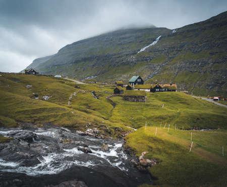 Lonely seaside house between the foggy green mountains, Faroe islands, Saksun village