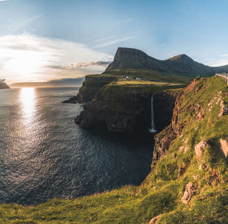 Gasadalur village and Mulafossur its iconic waterfall during summer with bluw sky. Vagar, Faroe Islands, Denmark. Rough see in the north atlantic ocean.