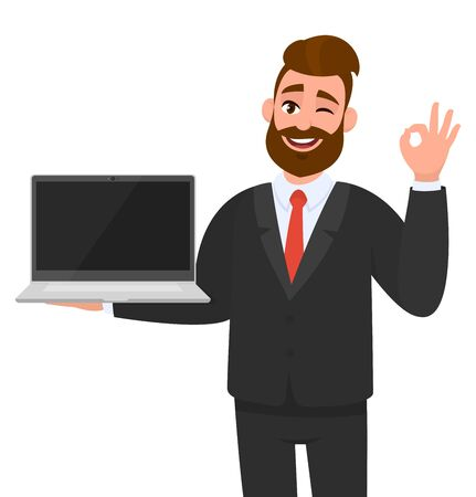 Smiling business man holding or showing a new brand, blank screen laptop computer (PC) and gesturing, making okay, OK, cool sign while winking eye. Modern lifestyle, digital technology device, gadget.