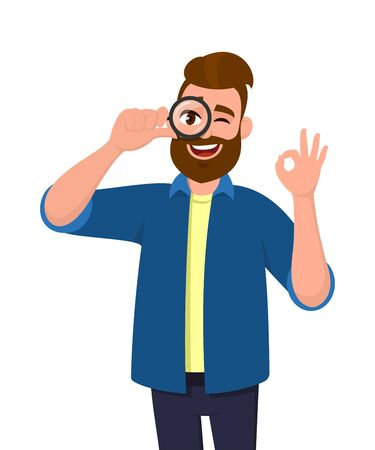 Young man looking through magnifier and showing okay gesture while winking eye. Trendy person holding magnifying glasslens and making OK sign. Male character with loupe. Vector illustration cartoon.