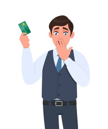 Shocked young businessman showing credit card and covering mouth with hand. Frustrated person in waistcoat holding debit, ATM card. Stylish male character design illustration in vector cartoon style. Stock Illustratie