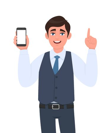 Young businessman in vest suit showing a blank screen mobile phone and pointing finger up. Person holding white display smartphone for mock up template. Male character illustration in vector cartoon.