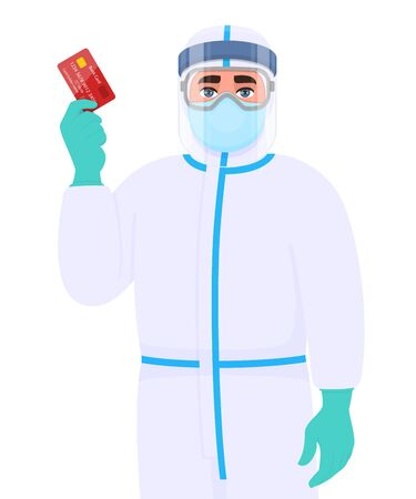 Person in safety protection suit, medical mask, glasses and face shield showing credit, debit, ATM card. Doctor or physician holding banking card. Surgeon wearing personal protective equipment (PPE).