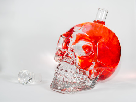 Glass skull with red and orange ink drops in water, alcohol