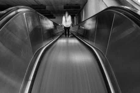 Lonely woman standing on an escalator
