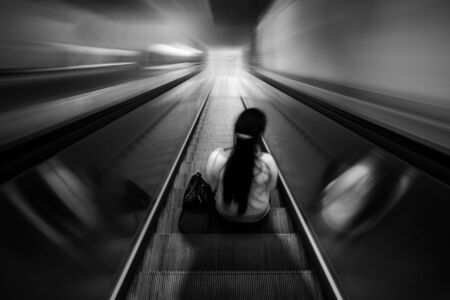 Lonely woman sitting on an escalator