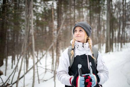 Vorderansicht einer Frau, die beim Schneeschuhwandern eine Pause macht