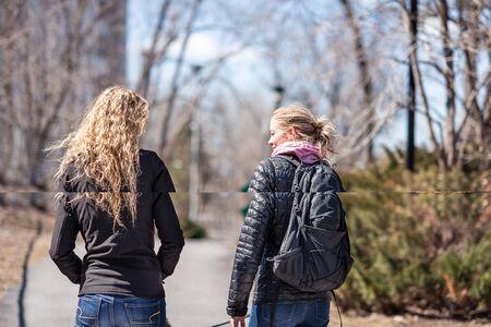 Two blond women friends walking a dog 免版税图像