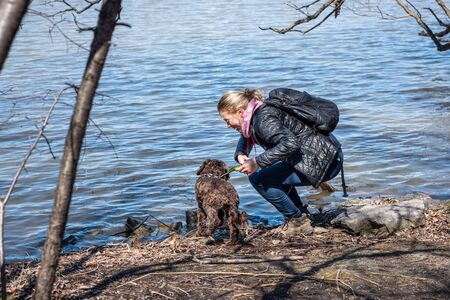 Blond young woman playing with a dog next to a river