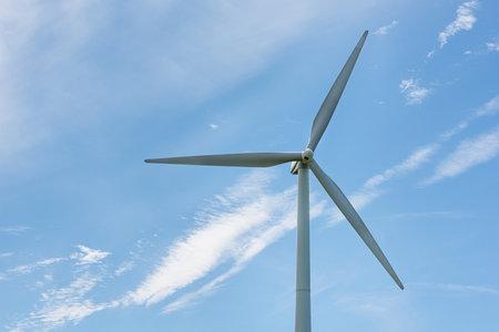 Close-up of a white wind turbine on a blue sky