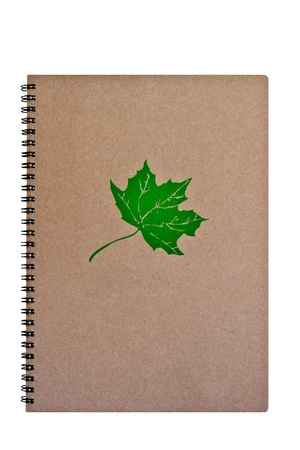 Brown notebook with green leaf, isolated on white background photo