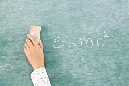 Hand with eraser on green chalk board (blackboard)