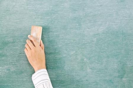 緑のチョーク ボード (黒板) 上に消しゴムを手