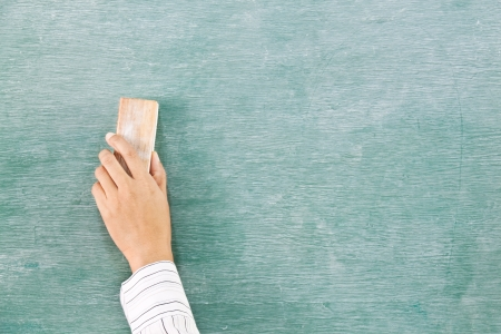 Hand with eraser on green chalk board  (blackboard) Stock Photo