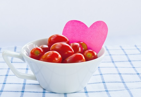 Cup of fresh tomatoes with pink heart