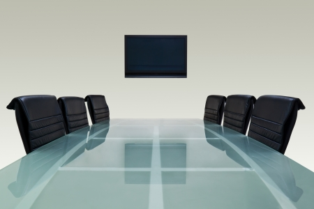 table glass: Meeting room with glass top table , armchairs and television