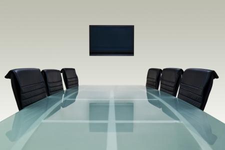 Salle de réunion avec table en verre haut, fauteuils et télévision