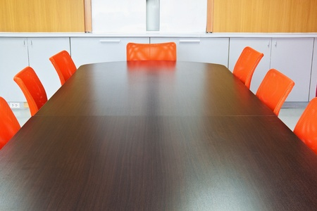 board room: Meeting room with brown table , orange armchairs and wood wall