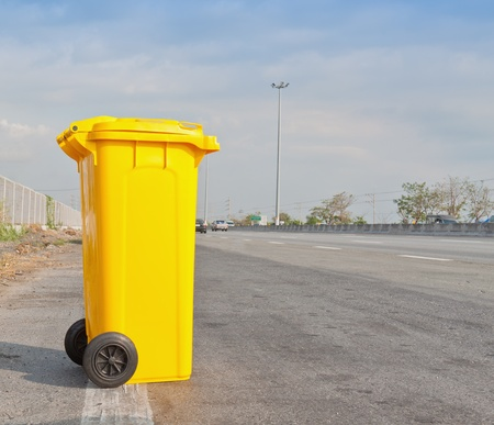 trash can: Yellow clean garbage bin on highway