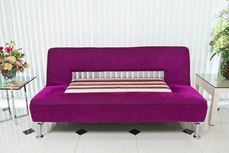 Purple sofa in lobby with small tables and flower photo